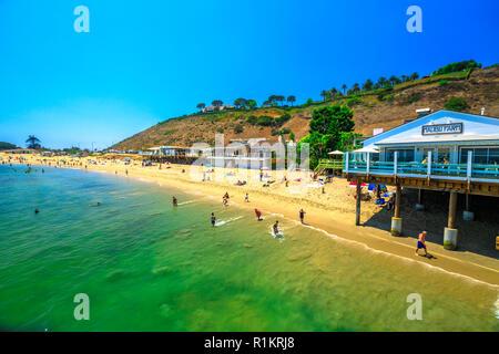 Malibu, California, United States - August 7, 2018: scenic coastal landscape with Santa Monica Mountains, Malibu Farm Restaurant and turquoise sea of Surfrider Beach. Malibu 27 miles of scenic beauty. - Stock Photo