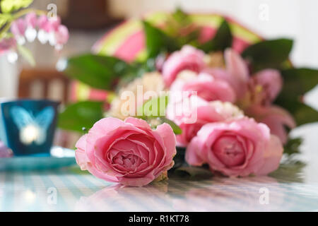 pink colored roses in a bouquet of flowers are on the table. Light blue elements are out of focus. - Stock Photo