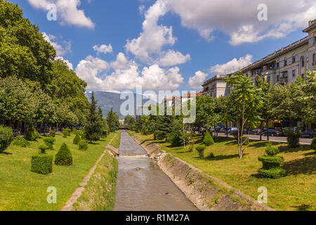 Tirana, Albania - 30 June 2014: Lana River in the center of Tirana. Skyscraper and mountains in the background. Tirana is the capital and most populou - Stock Photo