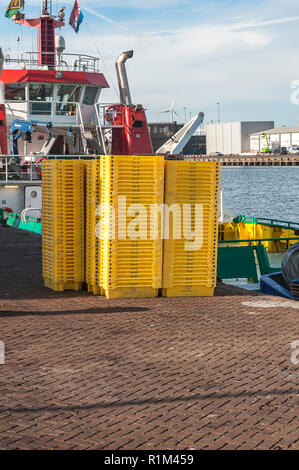 yellow empty plastic fish crates piled up at the harbour - Stock Photo