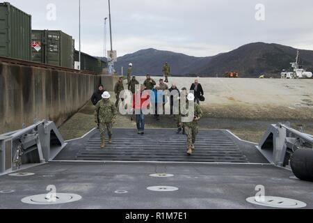 (Oct. 17, 2018) - Local Norwegian media personnel embark onboard an Improved Navy Lighterage causeway ferry, operated by Naval Beach Group 2, in order to view the launch of the 2nd Assault Amphibian Battalion, 2nd Marine Division, assault amphibious vehicles from the stern of USNS 1st Lt. Baldomero Lopez (T-AK 3010) during Exercise Northern Screen in Bogen, Norway, Oct. 17, 2018. Northern Screen is a bilateral exercise involving the United States Marine Corps' Marine Rotational Force-Europe (MRF-E) and Norwegian military, and is taking place in vicinity of Setermoen, Norway, from Oct. 24 to No - Stock Photo