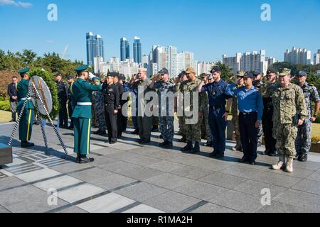 BUSAN, Republic of Korea (Oct. 19, 2018) Service members representing the U.N. Sending States participate in a wreath-laying ceremony at The U.N. Memorial Cemetery in Korea, as a formal conclusion to the Mine Countermeasures Symposium. The ceremony was held in remembrance of Sending States members who fought in the Korean War and are interred at the cemetery. - Stock Photo