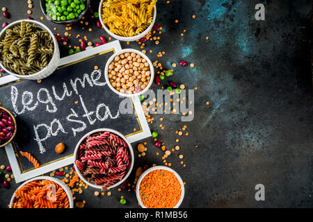 Trend healthy food, vegan diet concept. Multi colored legume pasta with raw beans. Beans, chickpeas, green peas, lentils. Copy space top view - Stock Photo
