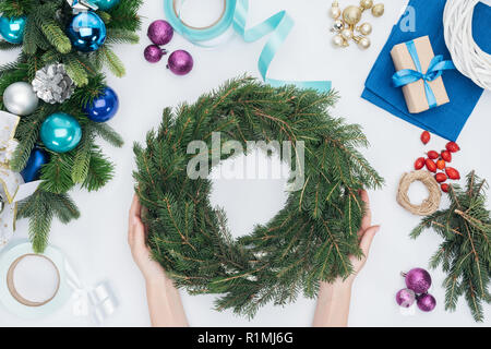 partial view of woman holding handmade pine tree wreath at tabletop with chrismtas decorations - Stock Photo