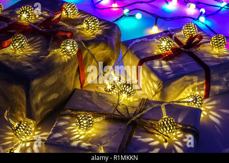 Christmas gift boxes on blue background. Burlap canvas and white wrapping paper with red ribbon.  Gold decoration lights. - Stock Photo