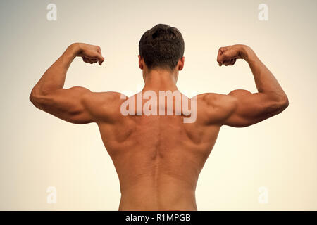 Man or sportsman flexing arms with fists, back view. Bodybuilder showing muscles, biceps and triceps. Athlete with bare torso on white sky. Fitness and sport. Healthy lifestyle concept - Stock Photo