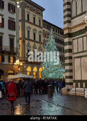 FLORENCE, TUSCANY ITALY - December 28, 2017,  Christmas tree illuminated standing near Florence Cathedral, tourist in line for Florence Bapristery ent - Stock Photo