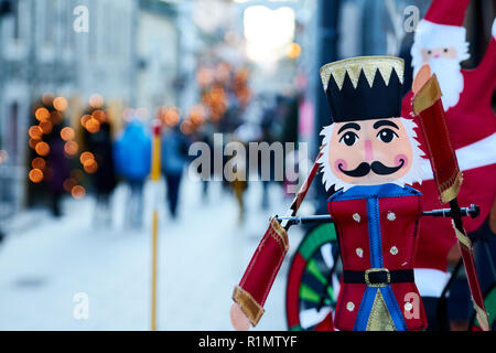 QUEBEC CITY - CANADA December 30, 2014.  Nutcracker figurine on a street with snow and people walking in the background, stores with christmas lights  - Stock Photo
