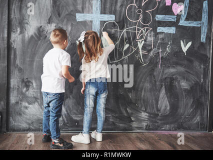 Cute little girl and boy drawing with crayon color on the wall. Works of child. Cute pupil writing on chalkboard - Stock Photo