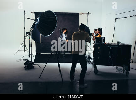Photographer shooting photos of a female model with studio flash lights on. Photographer with his team during a photo shoot. - Stock Photo