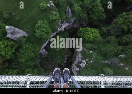 Man Feet standing on the edge of suspension bridge in Khndzoresk - Stock Photo