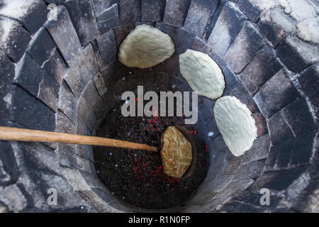 Traditional way of baking bread in the tandoor in Armeina - Stock Photo