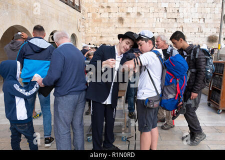 A young Lubavitcher Hasidic Jews helps another Jew put on tefillin at the Wailing Wall in Jerusalem, Israel. - Stock Photo
