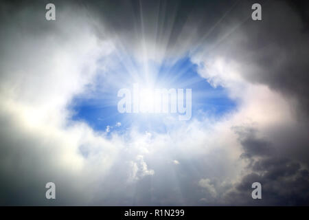 sun shining through hole in clouds - Stock Photo