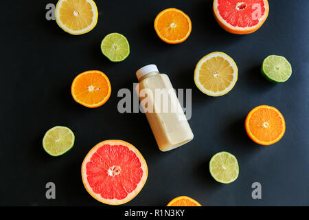 Variety of whole and sliced citrus fruits grapefruit, lemon, lime, bottle of juice in bowl over gray textured background. Top view with space. - Stock Photo