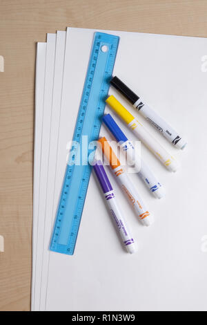 School and art supplies including color markers, a blue ruler, and white tag board on a desktop - Stock Photo