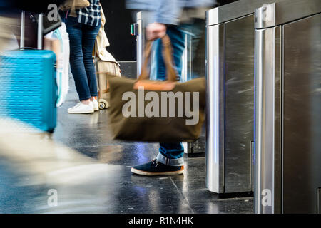 People with bags and rolling suitcases passing through stainless steel ticket gates in a public transportation station in Paris with motion blur. - Stock Photo