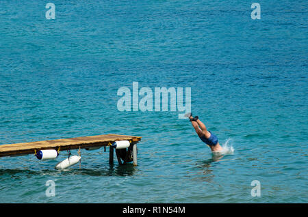 Man in a bathing suit dives into the sea from a wooden pier, wearing black rubber shoes - Stock Photo
