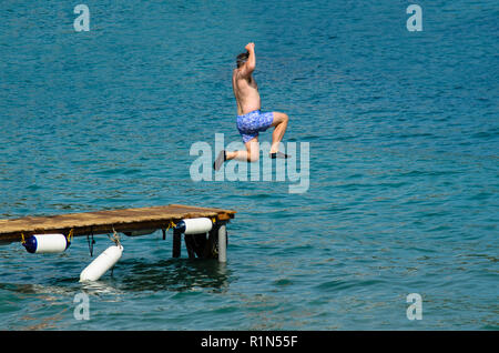 Man in swimsuit jumping into the sea from a wooden pier, wearing black rubber shoes - Stock Photo
