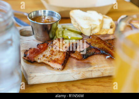 Close up view of charcuterie board on a restaurant table with several different types of artisanal bacon - Stock Photo