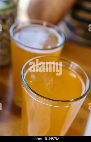 Close up of two tall glasses of beer on a table at a restaurant - Stock Photo