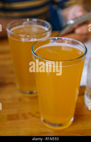 Close up of two tall glasses of beer on a table at a restaurant with person holding mobile phone in background - Stock Photo