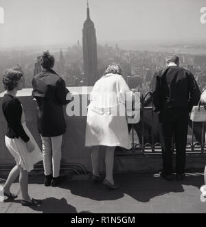 1950s, historical, 'Don't look down!'... tourists standing on a viewing balcony or observation deck on top of a tall building in Manhattan, New York, USA, lean over the edge to get a view of the city below One of the city's most famous skyscrapers, the Empire State Building can be seen in the distance. - Stock Photo