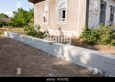 Building concrete foundation for wooden rural fence. Foundation for fence. - Stock Photo