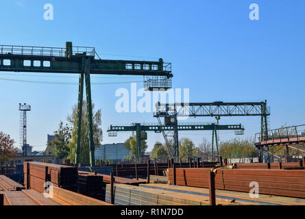 Warehouse of metal products, metal, on the background of a gantry crane on an industrial site - Stock Photo