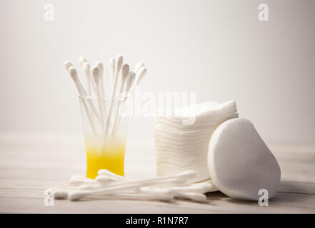 Clean cotton pads and sticks in a glass for the body on a light background, the concept of care facial - Stock Photo