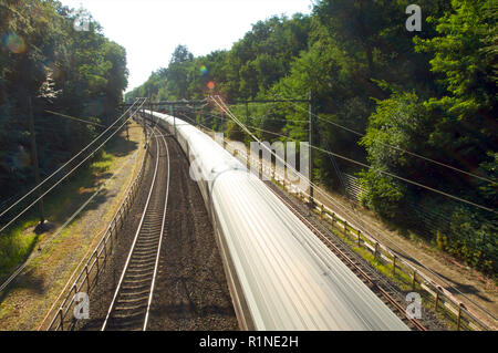Train traveling fast between Baarn and Hilversum passing through a forest area with great speed, the Netherlands - Stock Photo