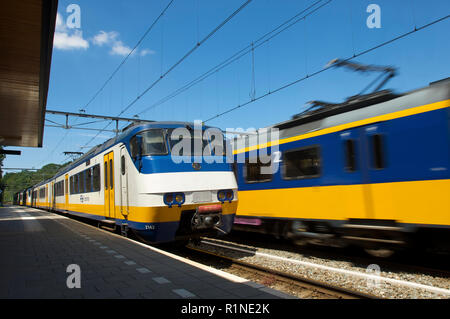A waiting sprinter train and a passing intercity train at the railway station in Baarn, the Netherlands - Stock Photo
