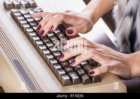 Woman hands typing on old computer keyboard on desk in office. Retro and vintage information technology concept. Close up, selective focus - Stock Photo