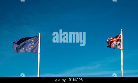 Brexit. Frayed and faded flags of the United Kingdom and the European Union flap in a blue sky - Stock Photo