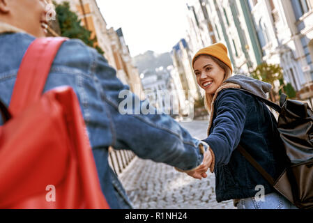 Traveler couple bloggers in love are enjoying view of old city. Rear view - Stock Photo