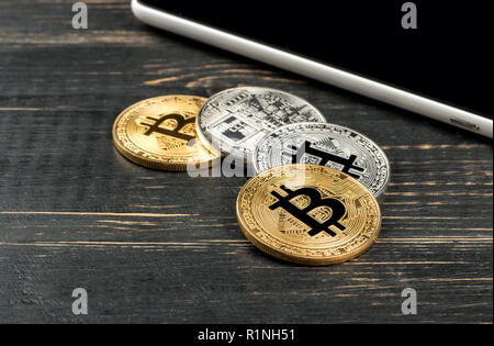 Gold and silver coins bitcoin with a tablet on wooden background - Stock Photo