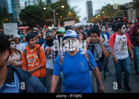 People march through Mexico City during the 'Global Day of Action for Ayotzinapa' Wednesday, October 23, 2014.  The march was held to demand answers following the killing of three students and the disappearance of 43 more in the city of  Ayotzinapa, Guerrero, which is South West of Mexico City.  The students have been missing since September 26, 2014 and the local mayor and his wife are accused of ordering the kidnappings and killings. The local police are also accused of working with  the Guerreros Unidos cartel in the crimes.   Since September 26, many mass graves have been located in the ar - Stock Photo