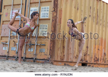 Young woman doing yoga on the beach the dancer's pose or Natarajasana - Stock Photo