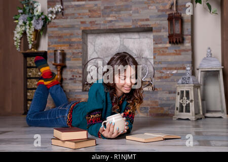 Woman reading a book and enjoying a hot chocolate by the fireplace. lying on the floor.heated floor, floor heating concept. reading book and drinking hot drinks.Woman resting with tea and book - Stock Photo