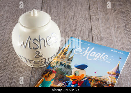 Savings Jar with a Walt Disney World Travel Brochure - Stock Photo