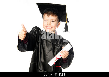 A Young boy 4 years old in graduation dress for the nursery class - Stock Photo