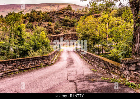 Old bridge over the river Ax-les-thermes near the village with the same name in the French Pyrenees and neighboring Andorra. Ariege France - Stock Photo