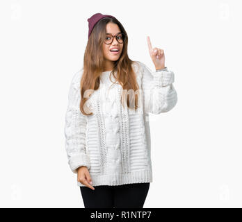 Young beautiful brunette hipster woman wearing glasses and winter hat over isolated background pointing finger up with successful idea. Exited and hap - Stock Photo