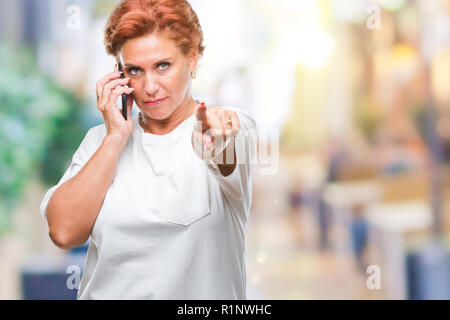 Atrractive senior caucasian redhead woman talking on smartphone over isolated background pointing with finger to the camera and to you, hand sign, pos - Stock Photo