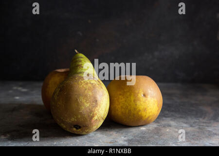 a pear and two russett apples on a grey textured background with darker lighting creating a moody dark feel to the image - Stock Photo