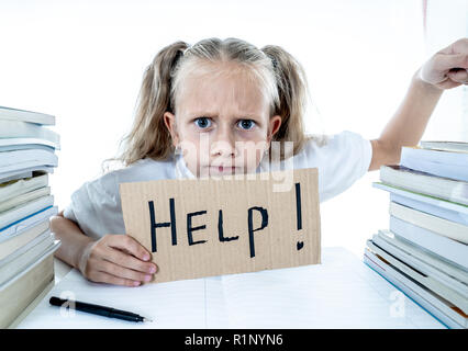 Angry little girl with a negative attitude towards studies and school after studying too much and having too many homework in children education conce - Stock Photo