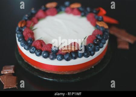 blueberries raspberries handmade cake with berries, cheesecake on a black background, - Stock Photo