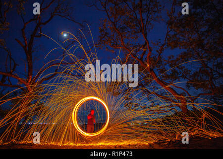 long exposure speed motion abstract of steel wool at twight beside mangrove forest - Stock Photo