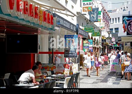 Tourists relaxing at a pavement cafe in the old town with shops and shoppers to the rear, Albufeira, Algarve, Portugal, Europe. - Stock Photo