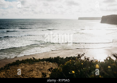 Beautiful views of the Atlantic Ocean and coastal cliffs and plants or vegetation off the coast of Portugal on a sunny day. People surf in the water. Selective focus. - Stock Photo